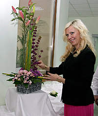"Olga Uskova poses next to an arrangement, work of Johann Liher, during the opening of center for flowers ""Tilia"""